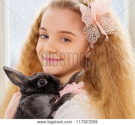 Beautiful little girl sitting on a windowsill and playing with Easter bunny.
