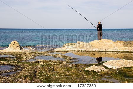 The fisherman is fishing on the shore of the Mediterranean Sea