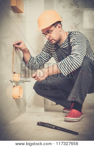 Builder measuring pipe in a bathroom