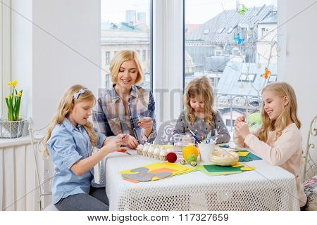 Cheerful mother and her daughters painting and decorating easter eggs.