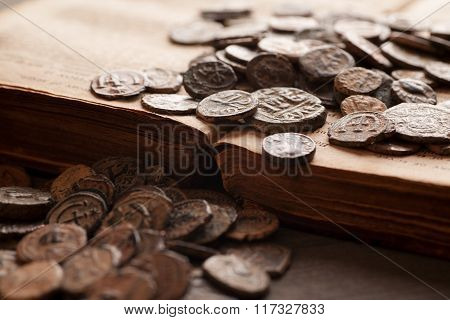 Pile Of Ancient Coins On The Very Old Book