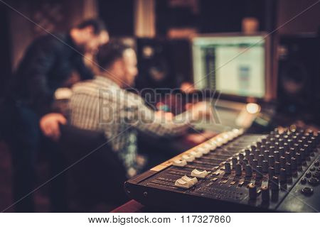 Sound engineer and producer working together at mixing panel in the boutique recording studio.