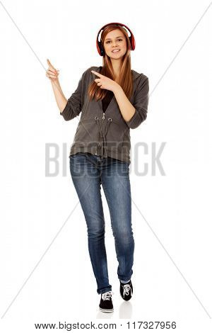 Happy teenage woman pointing for something