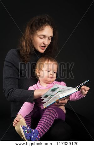 mother with daughter reading book over black
