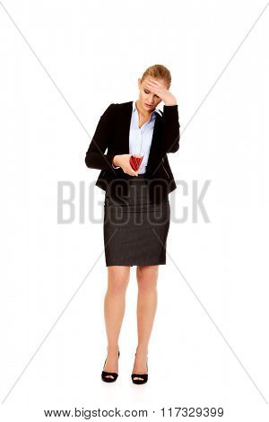 Worried business woman looking into her empty wallet