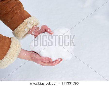 Female hands full of snow, winter season concept.