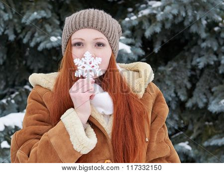 Girl portrait at winter forest, snowy weather, showing big snowflake toy.