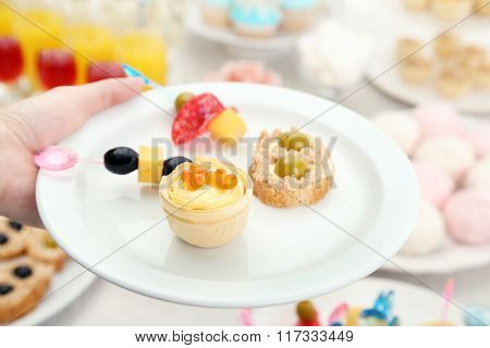 Woman holding plate with snacks and canape on buffet background