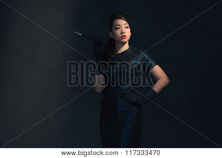 Posh Asian Woman In Retro 1940 Dress Smokes Cigaret.