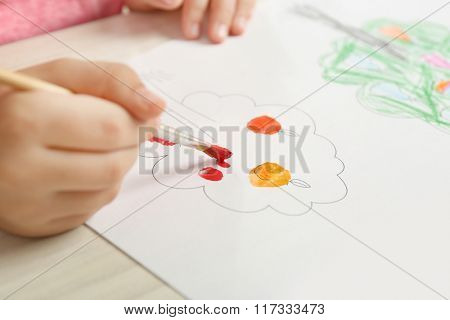Child drawing tree with bright paints on paper, closeup