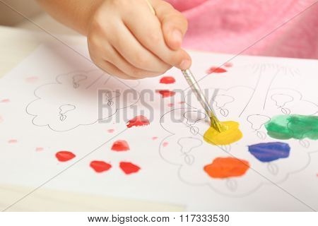 Child drawing with bright paints on paper, closeup