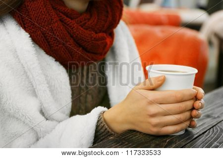 Female hands holding a cup of hot drink at the table