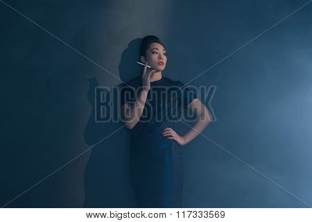 Retro 40S Styled Asian Woman In Evening Dress Smoking Cigarette. Leaning Against Wall.