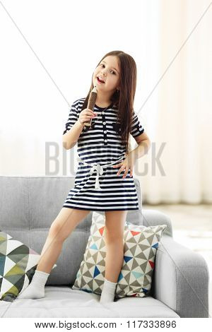 Beautiful little girl singing in a wooden pencil and has fun in the room