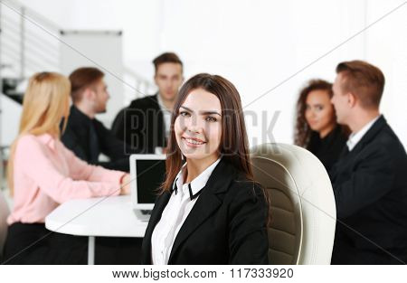 Photo of business woman with her staff in conference room at the meeting