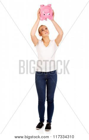 Sad young woman shaking piggybank for coins