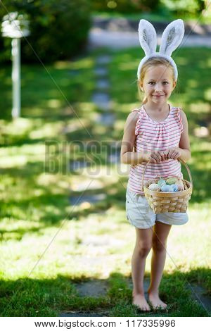 Adorable little girl wearing bunny ears holding a basket with Easter eggs outdoors on spring day