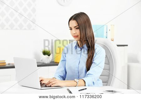A beautiful successful woman working at the modern office