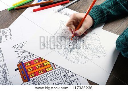 Female hand painting anti stress colouring with orange felt pen