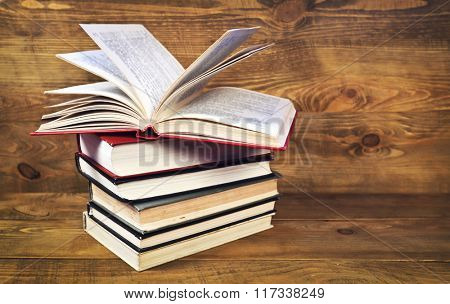 Open book on stack of books on wooden table
