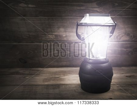 One camping lamp sjine bright on wooden table in the dark
