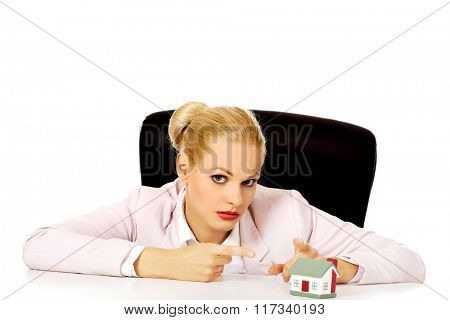 Business woman sitting behind the desk and pointing for house model