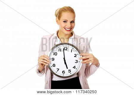 Smiling young business woman holding office clock