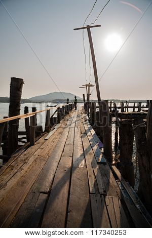 Morning on the sea coast of Phuket island, Thailand. On a wooden pier is a boy.