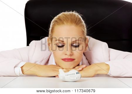 Smile business woman lying on the desk and looking for toy plane