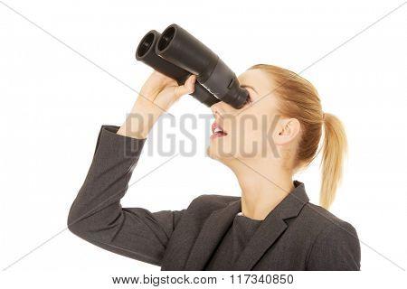 Businesswoman looking through binoculars.