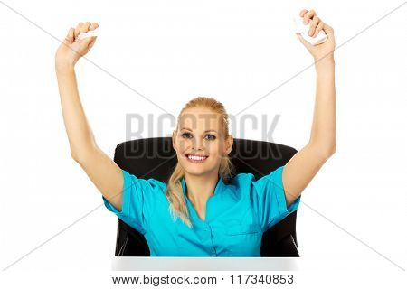 Funny female nurse or doctor sitting behind the desk and holding developed bandage above her head