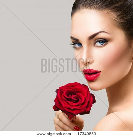 Beauty Fashion Model Woman face. Portrait with Red Rose flower. Red Lips and Nails. Beautiful Brunette Woman with Luxury Makeup and Manicure