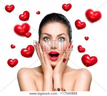 Beauty Fashion surprised Woman with flying red hearts. Love concept, Valentine's Day. Beautiful model girl with perfect make up exited and open and mouth. Isolated on a white background