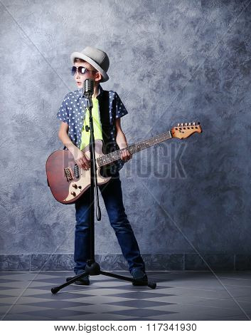 Little boy playing guitar and singing with microphone on a grey wall background