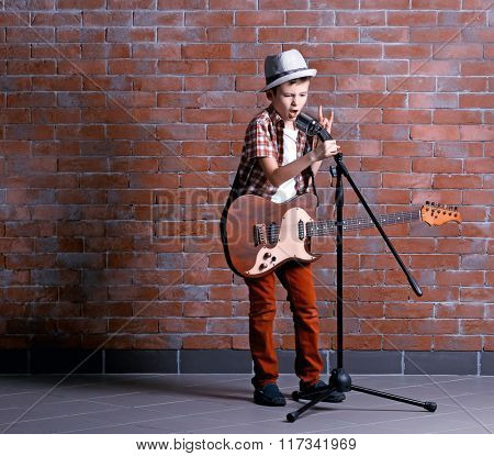 Little boy playing guitar and singing with microphone on a brick wall background