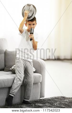 Little boy in a hat singing into the microphone at home