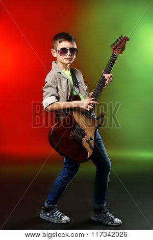 Little boy playing guitar on a bright background