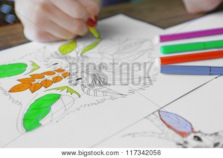 Female hand painting anti stress colouring with yellow felt pen