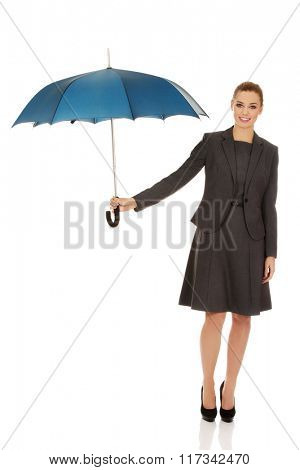 Business woman is holding blue umbrella