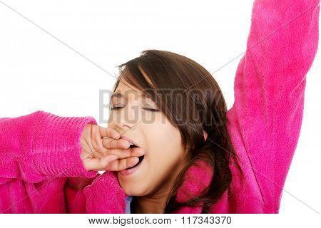 Beautiful yawning woman in pink bathrobe.