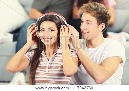 Teenager couple listening to music with headphone in living room