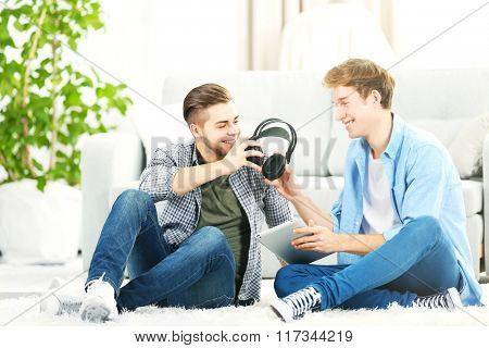 Two teenager boys listening to music with laptop and headphones in living room