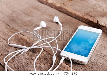 White cellphone with romantic screensaver and headphones on wooden background