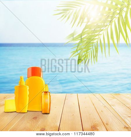 Bottles with suntan cream, lotion and spray on wooden board on sea background