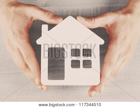 Male hands holding model of house on wooden background, close-up