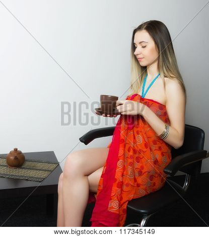 beautiful  young woman in bikini and pareo sitting on a chair and drinking coffee in brown cup