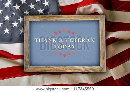 Text Thank A Veterans Today in frame on American flag background