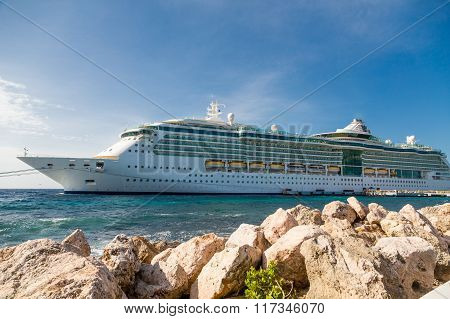 Cruise Ship Moored In Curacao Beyond Seawall