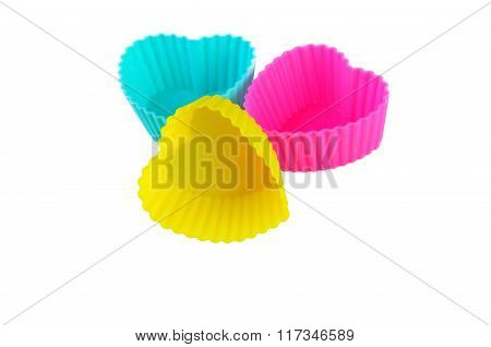 Three Multicolor Silicone Muffin Pans On A White Background