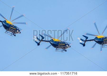 Three Police Helicopter Flying Against A Clear Blue Sky